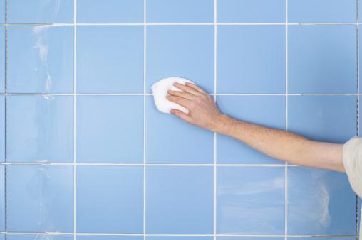 técnica limpiará los azulejos del baño